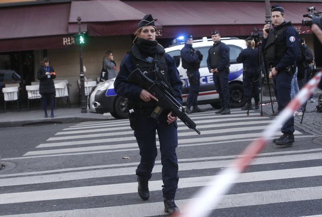 Police officers take position outside the Louvre museum in Paris,Friday, February 3, 2017. Paris police say a soldier has opened fire outside the Louvre Museum after he was attacked by someone, and the area is being evacuated. (Photo by Thibault Camus/AP Photo)