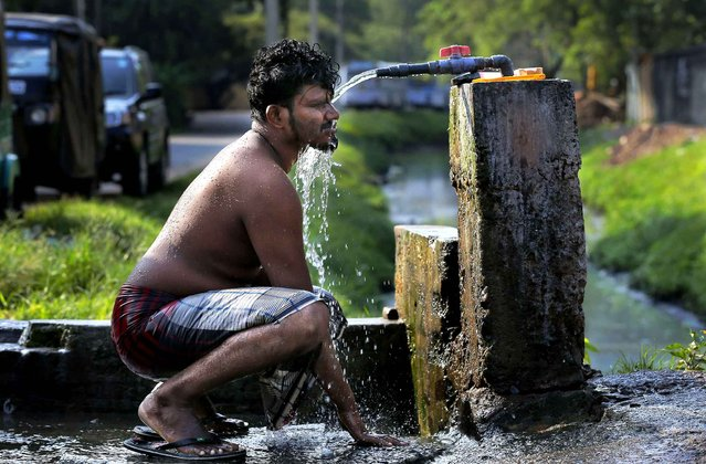 A Sri Lankan man takes a bath from a roadside tap to cool himself off from the rising temperature in Colombo, Sri Lanka, Monday, March 14, 2016. (Photo by Eranga Jayawardena/AP Photo)