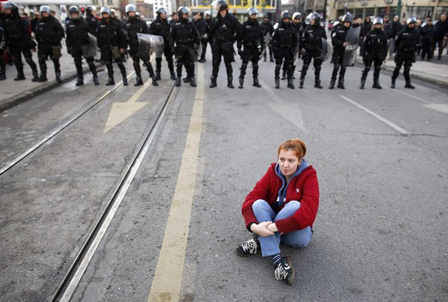 An anti-government protester sits on the ground in front of police during a demonstration in Sarajevo February 6, 2014. Hundreds of people turned out in solidarity in the capital Sarajevo, with teenagers throwing eggs and stones at a government building and fought with police. Four officers were taken to hospital, officials said. (Photo by Dado Ruvic/Reuters)