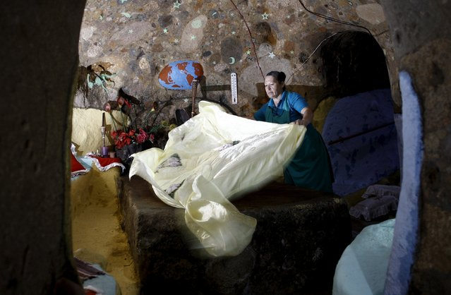 Cristal Barrantes makes a bed in her bedroom at the house that her husband Manuel Barrantes built underground in San Isidro de Perez Zeledon, Costa Rica, March 14, 2016. (Photo by Juan Carlos Ulate/Reuters)