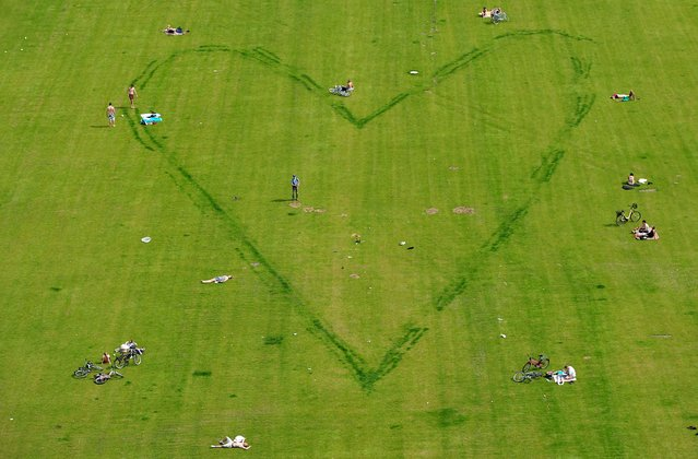 People sit around the contour of a heart scratched into a lawn in the center of Berlin in June 2010. (Photo by Johannes Eisele/AFP Photo)