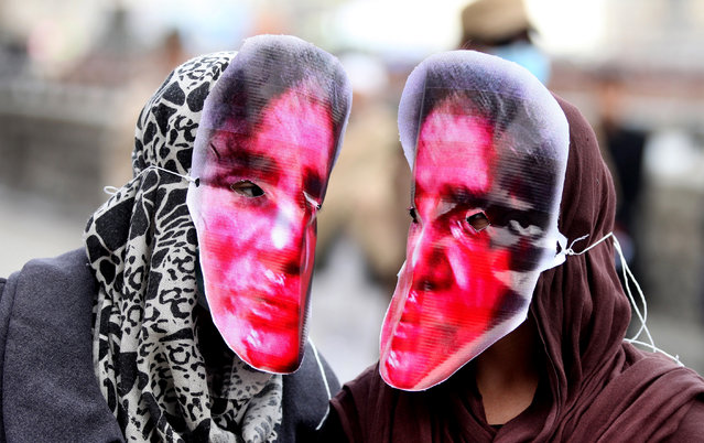 Afghan women wear mask of Farkhunda, an Afghan woman who was stoned to death by a mob, Kabul, Afghanistan, 17 March 2016. Farkhunda, 27, an Islamic Studies graduate, was killed by a mob outside a mosque on 19 March, after she was falsely accused of burning a Koran. She had been arguing with local mullahs about the selling of amulets for good fortune. The Appeals Court reduced the men's sentences to 20 years of jail. (Photo by Hedayatullah Amid/EPA)