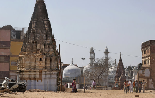 In this March 19, 2019, photo, 17th-century Gyanvapi mosque, white structure sandwiched between Hindu temples, is seen in the background as Hindu devotees walk at the site of a proposed grand promenade connecting the sacred Ganges river with a centuries-old temple dedicated to Lord Shiva, in Varanasi, India. And some Varanasi Muslims fear the project could embolden Hindu hard-liners who have demanded for decades that the 17th century Gyanvapi mosque – which they claim was built over an earlier Vishwanath temple demolished in the Mughal era – should itself be torn down. (Photo by Altaf Qadri/AP Photo)