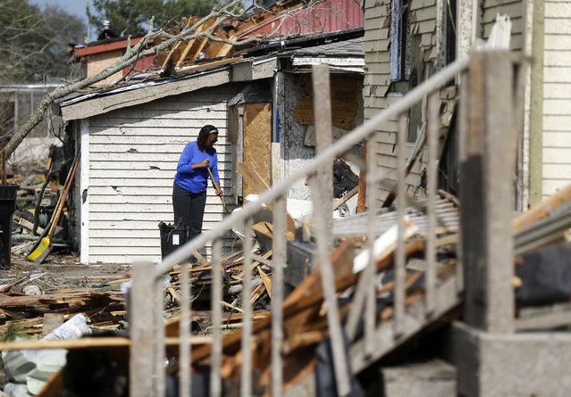 A woman clears debris from her damaged home in the aftermath of Tuesday's tornado that tore through the New Orleans East section of New Orleans, Wednesday, February 8, 2017.  Officials say tornadoes that struck in southeastern Louisiana destroyed homes and businesses, flipped vehicles and left thousands without power. (Photo by Gerald Herbert/AP Photo)