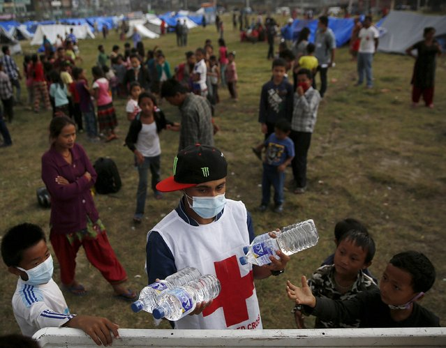 An aid worker distributes water at a camp for people displaced by the April 25 earthquake in Kathmandu, Nepal, May 7, 2015. (Photo by Olivia Harris/Reuters)