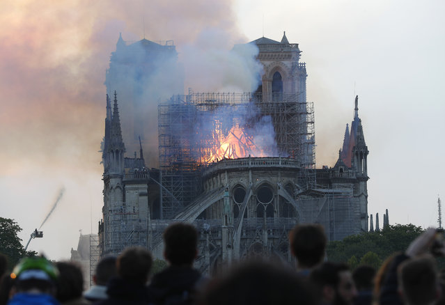 People watch as flames and smoke rise from Notre Dame cathedral as it burns in Paris, Monday, April 15, 2019. Massive plumes of yellow brown smoke is filling the air above Notre Dame Cathedral and ash is falling on tourists and others around the island that marks the center of Paris. (Photo by Thibault Camus/AP Photo)