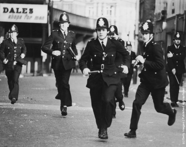 Police officers charge on the second day of rioting in Brixton, London, 13th April 1981