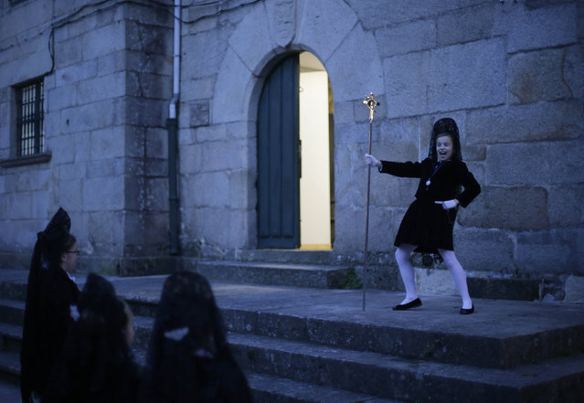 Girls play before the start of the 'Madre del Mayor Dolor' procession during the Holy Week in Pontevedra, northern Spain, March 23, 2016. (Photo by Miguel Vidal/Reuters)