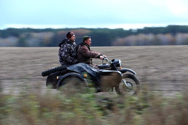 Vladimir Krivenchik (R) and Nikolay Skidan, hunters, ride a motorcycle near the village of Khrapkovo, Belarus November 4, 2016. (Photo by Vasily Fedosenko/Reuters)