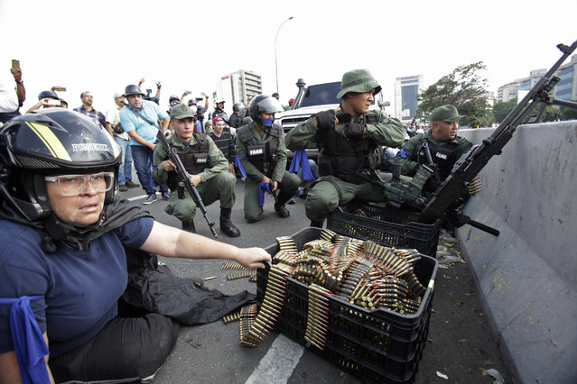 An anti-government protester sits by ammunition being used by rebel troops rising up against the government of Venezuela's President Nicolas Maduro as they all take cover on an overpass outside La Carlota military airbase where the rebel soldiers confront loyal troops inside the base in Caracas, Venezuela, Tuesday, April 30, 2019. (Photo by Boris Vergara/AP Photo)
