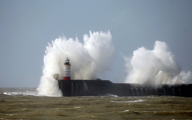 Waves crash against the lighthouse at Newhaven, England, Monday March 28, 2016. Some flights at London's Gatwick and Heathrow airports have been diverted due to high winds battering much of Britain and western France. The high winds from a storm caused 87 cancellations and 43 diversions at Gatwick and Heathrow because flights had trouble landing safely. (Photo by Steve Parsons/PA Wire via AP Photo)