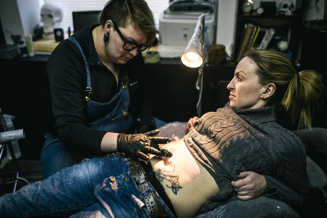 In this photo taken on Tuesday, January 31, 2017 Yevgeniya Zakhar gives a tattoo to Nadezhda, a victim of domestic violence. Yevgeniya Zakhar, a Russian tattoo artist from Ufa, a city about 1,200 kilometers (745 miles) east of Moscow, gives free tattoos to victims of domestic abuse, to cover their scars. The upper chamber of the Russian parliament last week passed a controversial bill decriminalizing some forms of domestic violence. (Photo by Vadim Braydov/AP Photo)
