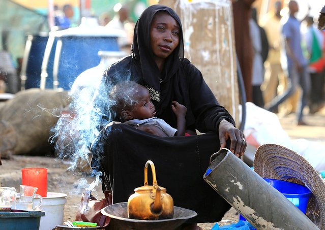 A Sudanese street vendor sells tea as she holds her baby in Khartoum, Sudan, April 30, 2019. (Photo by Umit Bektas/Reuters)