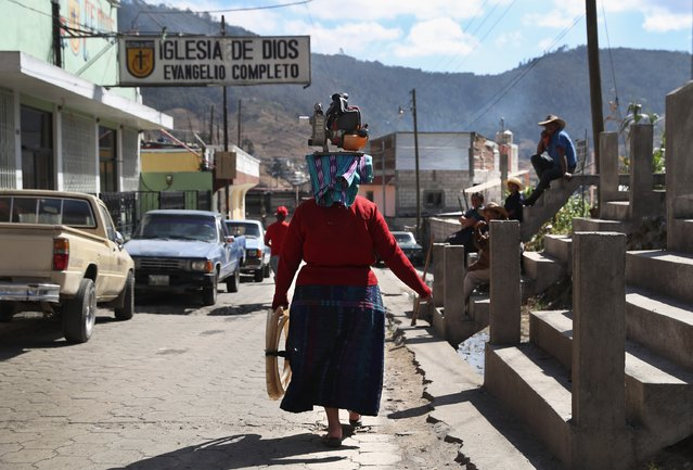 A woman carries a water pump to work on February 11, 2017 in Almolonga, Guatemala. (Photo by John Moore/Getty Images)
