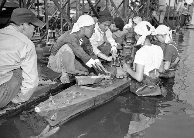 Japan's movie makers filming on the last day of the documentary about the Battleship Yamato. Studio men load shells into the guns of a model of the Yamato as they get it ready for the big scene on June 8, 1953. (Photo by Yuichi Ishizaki/AP Photo via The Atlantic)