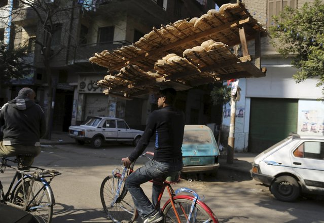 A bakery worker rides a bicycle as he carries fresh bread on his head in Cairo, Egypt, February 9, 2016. (Photo by Asmaa Waguih/Reuters)