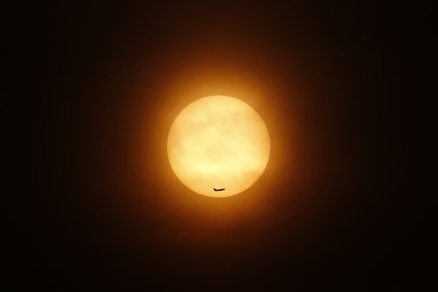 A passenger jet flies past the setting sun in Shanghai March 11, 2014. China has deployed 10 satellites to help in the massive air and sea search for a missing Malaysian airliner, the People's Liberation Army Daily said on Tuesday. (Photo by Aly Song/Reuters)
