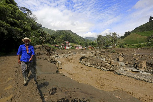 A resident walks in front of houses that were destroyed after a landslide sent mud and water crashing onto homes close to the municipality of Salgar in Antioquia department, Colombia May 19, 2015. (Photo by Jose Miguel Gomez/Reuters)