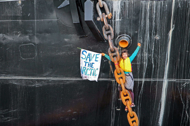 In this Friday, May 22, 2015 photo provided by Reese Semanko, a woman identified as Chiara D'Angelo has suspended herself in a climbing harness from the anchor chain of the Royal Dutch Shell support ship Arctic Challenger in the harbor at Bellingham, Wash. Rob Lewis, spokesman for protest organizers Rising Tide Bellingham, said she was protesting Shell's plan for Arctic drilling. (Photo by Reese Semanko via AP Photo)