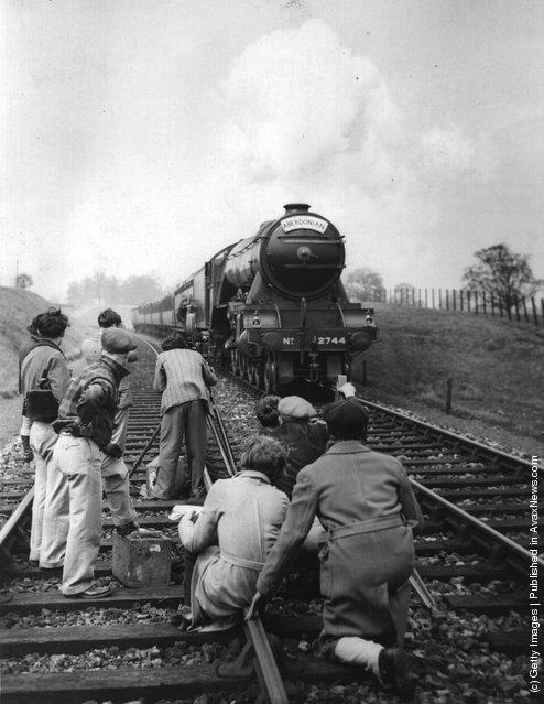 1934: Cameramen on the railway track getting a shot of the 'Aberdonian' express train, with an actor disembarking on to a tender, for the film 'Night Mail', directed by Herbert Smith