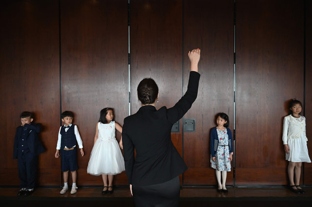This picture taken on June 1, 2019 shows Danielle Liu (2nd R) watching Miona Milakov (C) during an etiquette and manners class in central Shanghai. (Photo by Hector Retamal/AFP Photo)