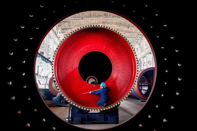 An employee measures a newly manufactured ball mill machine at a factory in Nantong, Jiangsu province, China on June 28, 2019. (Photo by Reuters/China Stringer Network)