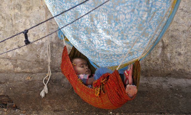 A child sleeps in a hammock along a sidewalk on a hot summer day in Ahmedabad, India, April 19, 2016. (Photo by Amit Dave/Reuters)