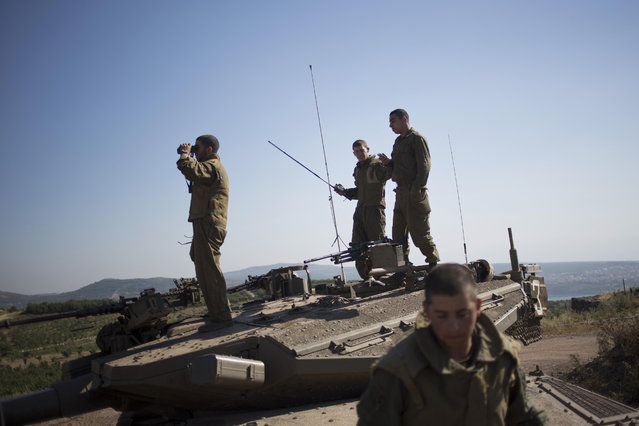 Israeli soldiers atop a tank watch smoke and explosions from the fighting between forces loyal to Syrian President Bashar Assad and rebels in the Druze village of Khader in Syria, as seen from the Israeli controlled Golan Heights, Tuesday, June 16, 2015. As many as 20 members of the Druze minority sect were killed last week, the deadliest violence against the Druze since Syria's conflict started in March 2011, sparking fears of a massacre against the sect. (AP Photo/Ariel Schalit)