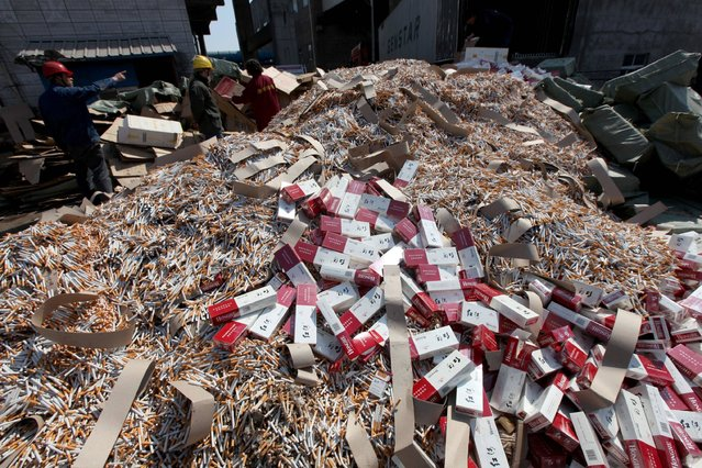 This photo taken on March 14, 2017 shows workers piling up fake and inferior cigarettes before being destroyed to mark World Consumer Rights Day in Xuchang, central China's Henan province. (Photo by AFP Photo/Stringer)