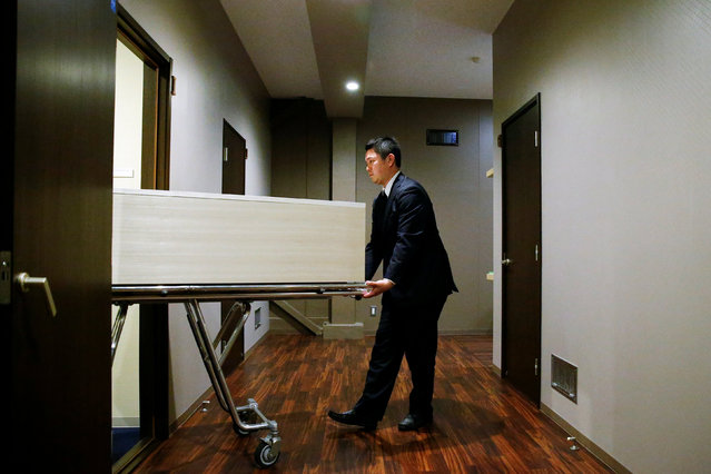 "A staff member removes a coffin from a room of the ""Corpse Hotel"" in Kawasaki, Japan, April 20, 2016. (Photo by Thomas Peter/Reuters)"
