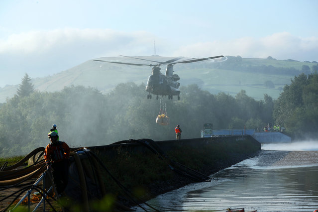 An RAF Chinook helicopter flies in sandbags to help repair the dam at Toddbrook reservoir near the village of Whaley Bridge in Derbyshire on August 2, 2019, after it was damaged by heavy rainfall. (Photo by Yui Mok/PA Images via Getty Images)