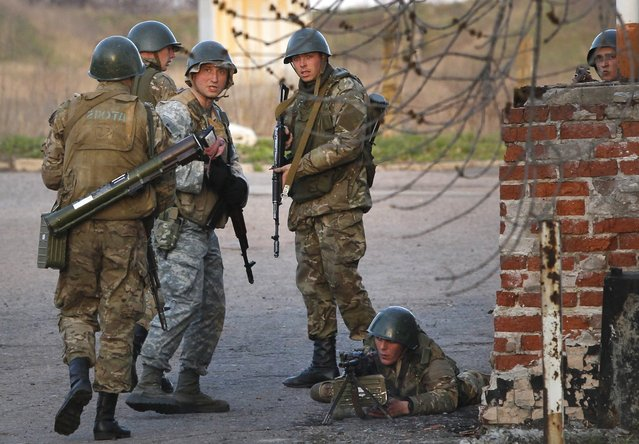 Ukrainian army troops set up a position at an airport in Kramatorsk, eastern Ukraine, Tuesday, April 15, 2014. In the first Ukrainian military action against a pro-Russian uprising in the east, government forces clashed Tuesday with about 30 armed gunmen at a small airport in Kramatorsk. (Photo by Sergei Grits/AP Photo)