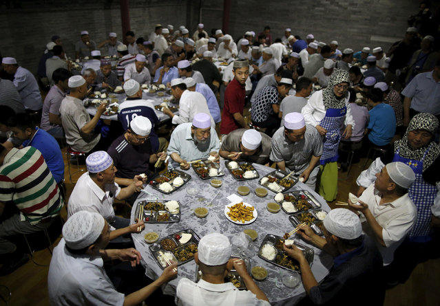 Muslims eat meals as they break fast on the first day of the holy fasting month of Ramadan at the Niujie Mosque in Beijing, China, June 18, 2015. (Photo by Kim Kyung-Hoon/Reuters)