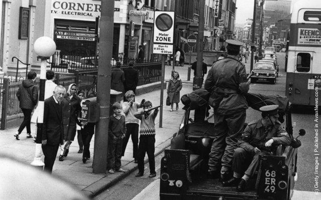 1970:  Children mocking an Army patrol in Belfast