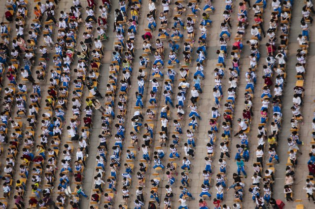 Students from different classes attend an outdoor joint lesson outside a school building in Guangzhou, Guangdong province April 18, 2014. (Photo by Alex Lee/Reuters)