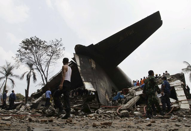 Security forces and rescue teams examine the the wreckage of an Indonesian military C-130 Hercules transport plane after it crashed into a residential area in the North Sumatra city of Medan, Indonesia, June 30, 2015. (Photo by Roni Bintang/Reuters)