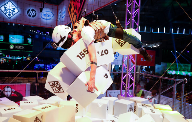 A blind-folded gamer collects as many as possible foam cubicles as he hangs from the ceiling at the first day of Europe's leading digital games fair Gamescom, which showcases the latest trends of the computer gaming scene in Cologne, Germany on August 21, 2019. (Photo by Wolfgang Rattay/Reuters)