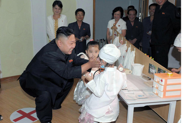 This undated picture released from North Korea's official Korean Central News Agency (KCNA) on July 15, 2012 shows North Korean leader Kim Jong-Un talking to two children as what seems to be the same woman (back L) who has recently been pictured accompanying Kim smiles during a visit to Kyongsang kindergarten in Pyongyang. (Photo by AFP Photo/KCNA via KNS)