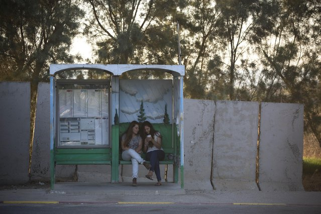 In this Tuesday, June 30, 2015. photo, Israeli girls wait for transportation in a bus stop protected with concrete blocks near the southern Israeli town of Sderot, next to the Israel-Gaza border. (Photo by Oded Balilty/AP Photo)