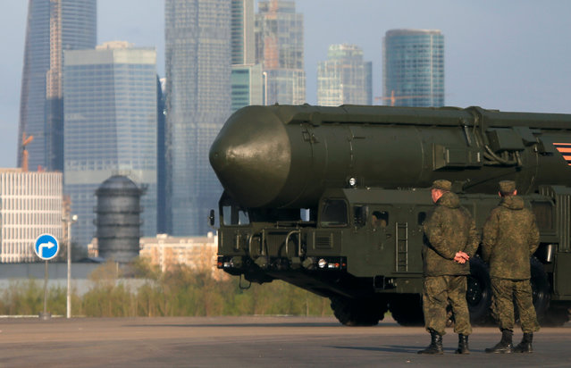 "Russian servicemen stand next to a Russian Yars RS-24 intercontinental ballistic missile system before a rehearsal for the Victory Day parade, with the Moscow International Business Center also known as ""Moskva-City"" seen in the background, at a range in Moscow, Russia, May 5, 2016. (Photo by Maxim Shemetov/Reuters)"