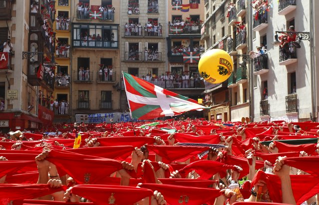 A Basque flag called the Ikurrina flies alongside traditional red scarves held up by revellers during the start of the San Fermin festival in Pamplona July 6, 2015. (Photo by Reuters/Stringer)