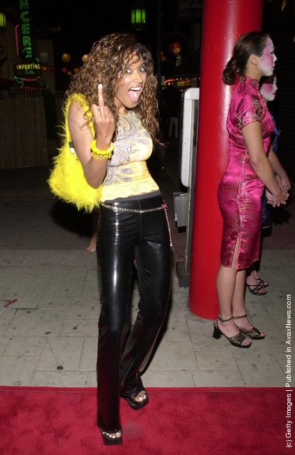 Actress Traci Bingham flips the finger for the photographer at Stuff Magazine's '7 Deadly Sins Escapade' party July 20, 2000 at the Old Chinatown section of Los Angeles, CA