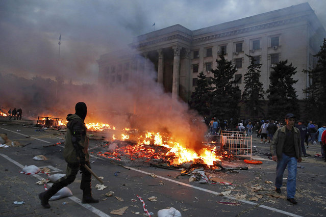 A protester walks past a burning pro-Russian tent camp near the trade union building in Odessa May 2, 2014. (Photo by Yevgeny Volokin/Reuters)