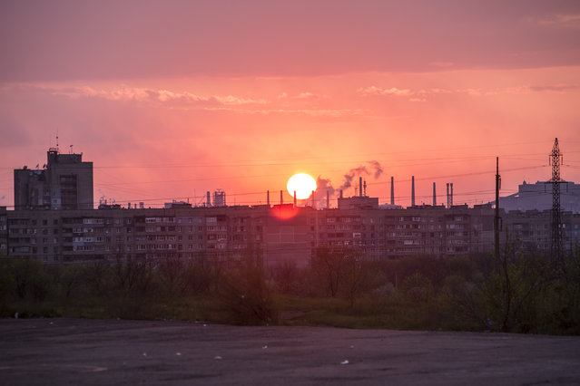 The sun sets behind apartment blocks and factory smokestacks on May 3, 2014 near Lukansk, Ukraine. Cities across Eastern Ukraine have been overtaken by pro-Russian protesters in recent weeks, leading the Ukrainian military to respond with force in some areas. (Photo by Brendan Hoffman for The Washington Post)