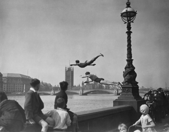 Two divers jumping off the Embankment into the River Thames in London, near Westminster Bridge on May 13, 1934. (Photo by H. F. Davis/Getty Images)