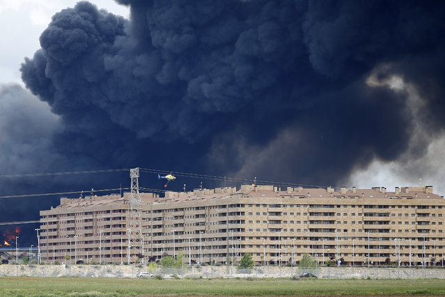 A fire fighting helicopter flies  billowing black smoke rising from behind large housing blocks in Sesena, central Spain, Friday, May 13, 2016. (Photo by Paul White/AP Photo)