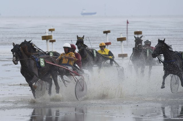 Competitors race on mud flats during their tideland race (Wadden Race) in Duhnen, Lower Saxony, Germany, July 12, 2015. (Photo by Fabian Bimmer/Reuters)