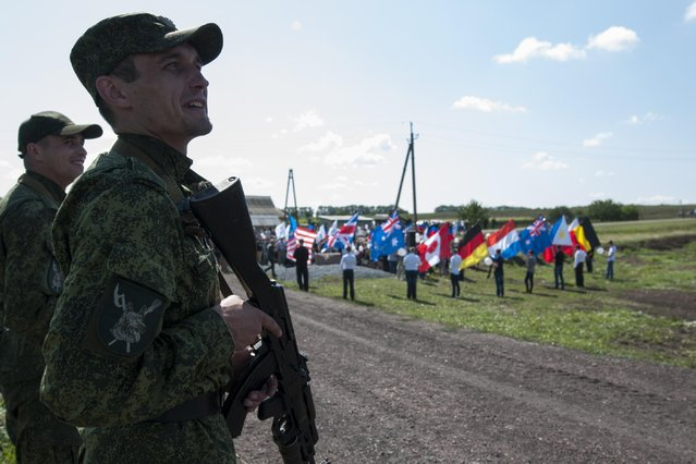 Russia-backed rebels stand guard as people holding flags of countries of the victims who were killed in the crash of the Malaysia Airlines Flight 17, gather for a memorial ceremony at the crash site near the village of Hrabove, eastern Ukraine, Friday, July 17, 2015. In the eastern Ukrainian village of Hrabove, residents carrying flowers gathered in a church for a memorial service and a procession at the crash site where a Malaysian airliner was shot down with 298 people aboard a year ago. (Photo by Antoine E. R. Delaunay/AP Photo)