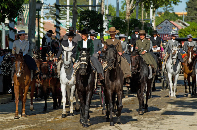 Participants in traditional dress ride on horseback as they enjoy the atmosphere at the Feria de Abril (April's Fair) on May 1, 2017 in Seville, Spain. The Feria de Abril, which has a story dating back to 1857, takes place a fortnight after Easter each year. The origin of the fair was a cattle market but the event quickly turned its goal from commerce to having fun. More than one million local and international participants are expected to attend to Feria de Abril. (Photo by David Ramos/Getty Images)