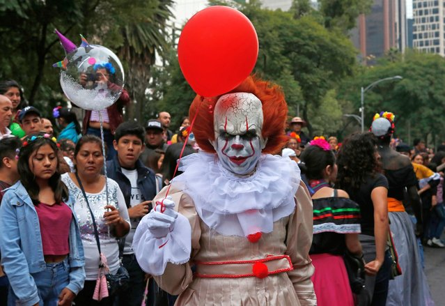 """A man wears the costume of what's known as """"It"""", a movie character, during the Catrinas parade down Mexico City's iconic Reforma avenue during celebrations for the Day of the Dead in Mexico, Saturday, October 26, 2019. (Photo by Ginnette Riquelme/AP Photo)"""